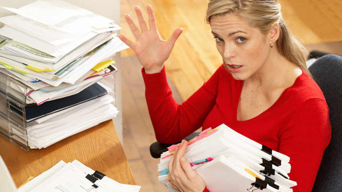 stressed female worker with pile of folders