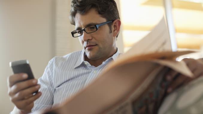 Premium: orang membaca smartphone dengan koran