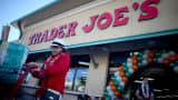A shopper exits with her groceries after shopping at the grand opening of a Trader Joe's in Pinecrest, Florida.
