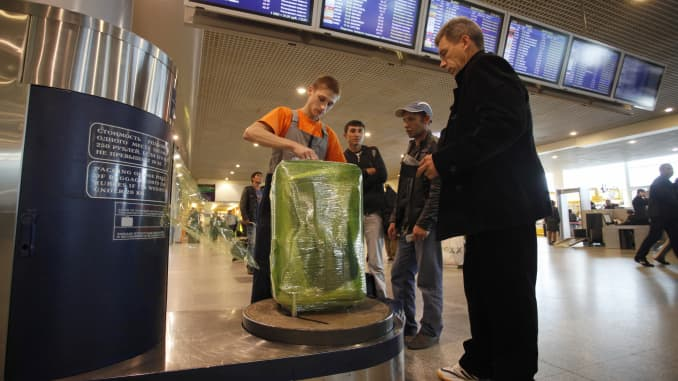 Travelers pay to protect luggage with plastic wrap