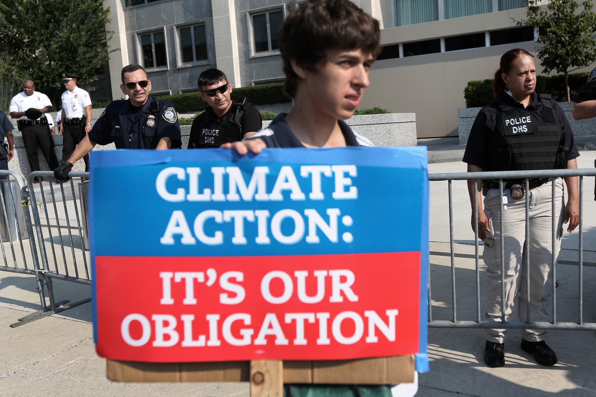 An activist holds a sign as he participates in a protest outside the U.S. State Department August 12, 2013 in Washington.