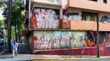 A man walks past a vacant building in the Santurce neighborhood of San Juan, Puerto Rico.