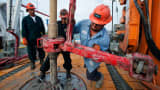 Workers make a pipe connection on the Orion Perseus drilling rig, Webb County, Texas.
