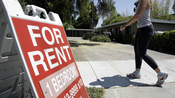 """A woman walks next to a """"For Rent"""" sign at an apartment complex in Palo Alto, California."""
