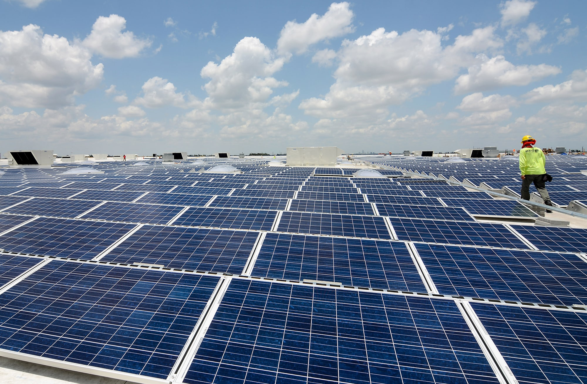A contractor walks past solar panels on the roof of a new IKEA store in Miami.