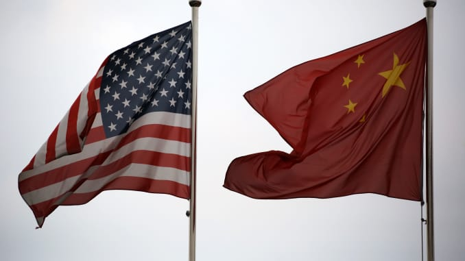 National flags of the U.S. and China fly outside a company building in the China (Shanghai) Pilot Free Trade Zone in Shanghai, China on Oct. 22, 2013.