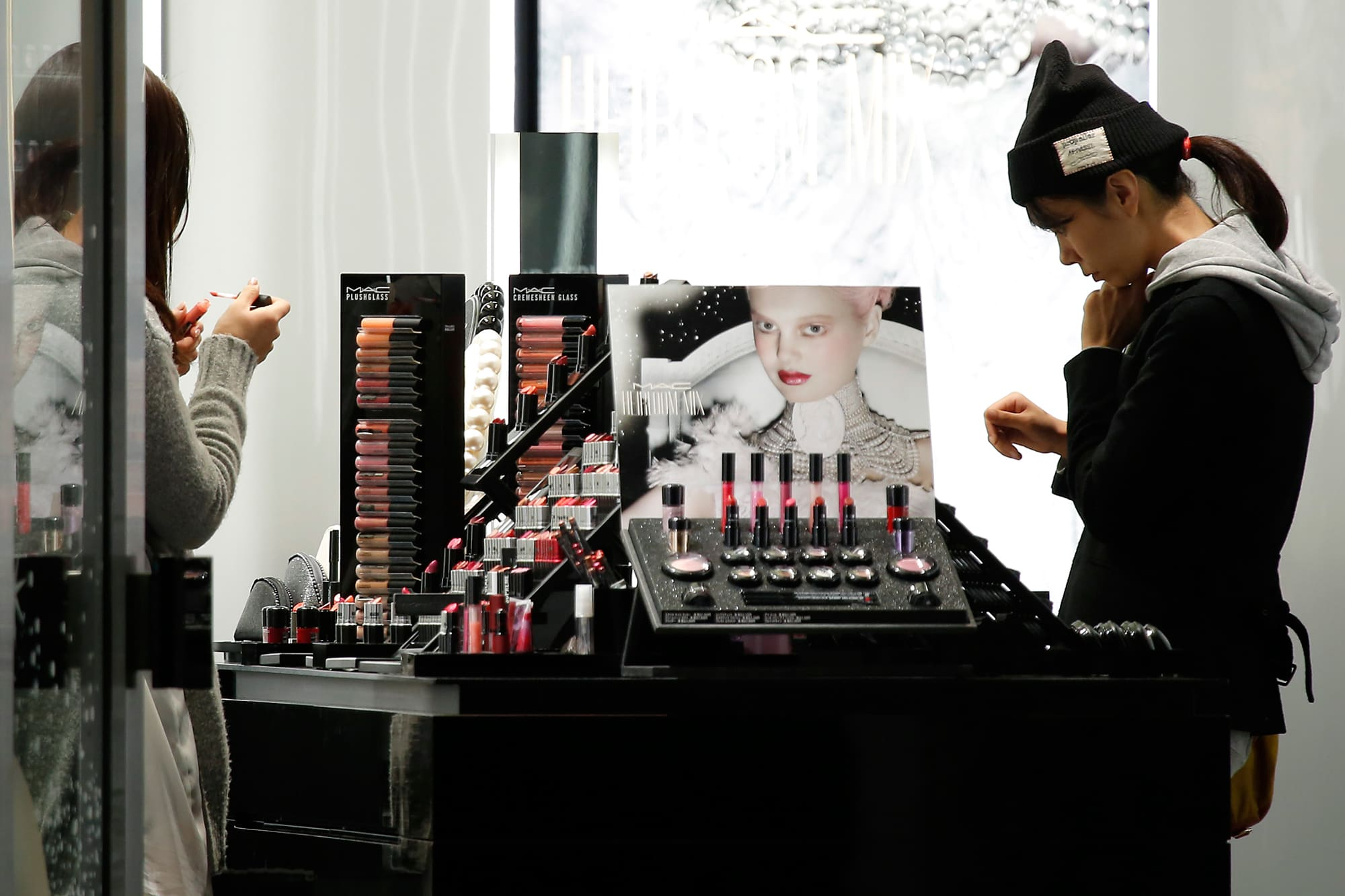 Young shoppers browse makeup products at an Estee Lauder MAC Cosmetics store.