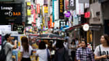 Shoppers and pedestrians walk past stores in the Myeongdong shopping district in Seoul, South Korea.