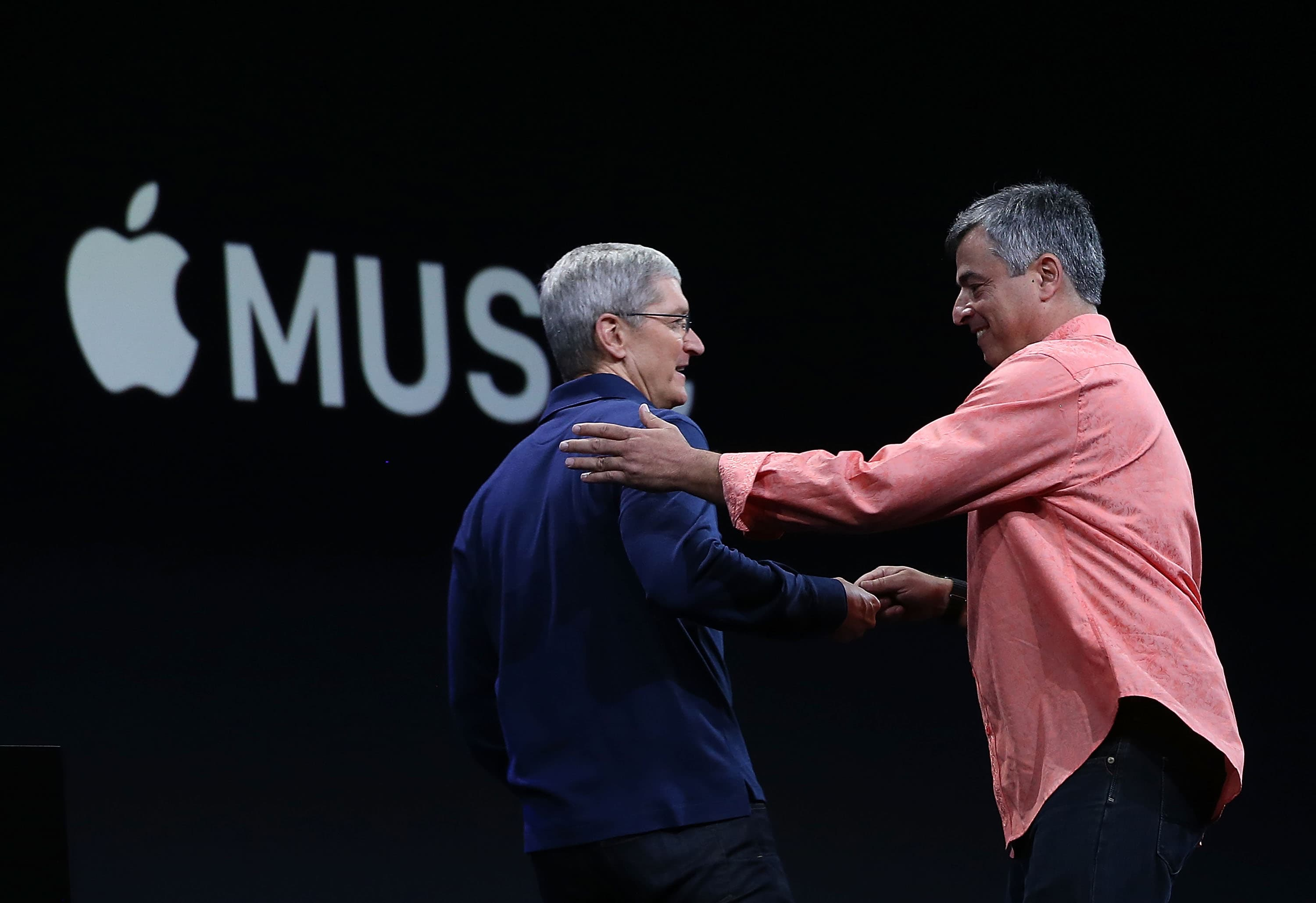 Apple's senior vice president of Internet Software and Services Eddy Cue (R) greets Apple CEO Tim Cook (L) during the Apple WWDC on June 8, 2015 in San Francisco, California.