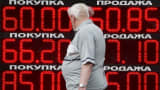 A man walks past a board showing currency exchange rates in Moscow, July 28, 2015.