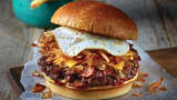Applebee's all-day brunch burger with bacon, onions, a fried egg, hash browns, American cheese and ketchup piled high on a bun.