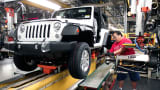 A worker installs tires on a Jeep Wrangler at the Chrysler Toledo North Assembly Plant in Toledo, Ohio.
