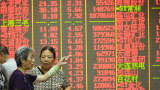 Stock investors monitor the trading boards in a stock exchange in China.