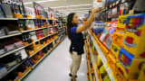 A Walmart department manager helps stock shelves with school supplies in San Diego.