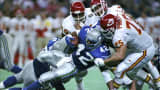 In this Nov. 22, 1992, file photo, Kansas City Chiefs' Tom Sims, rear left, Chris Martin, rear right, and Joe Phillips, right, tackle Seattle Seahawks running back Chris Warren during an NFL football game in Seattle. Five former Chiefs players are suing the team, claiming it hid the risks of head injuries.