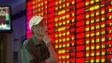 An investor observes stock market at a stock exchagne hall on September 22, 2015 in Nanjing, China.