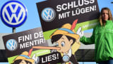 An activist holds up a sign reading 'Stop Lying' (Schluss mit Luegen) during a protest of environmental watchdog Greenpeace in front of the headquarters of German car maker Volkswagen in Wolfsburg, central Germany, on September 25, 2015.