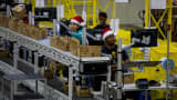 Amazon.com Inc. employees load boxes with merchandise at the company's fulfillment center in Tracy, California.