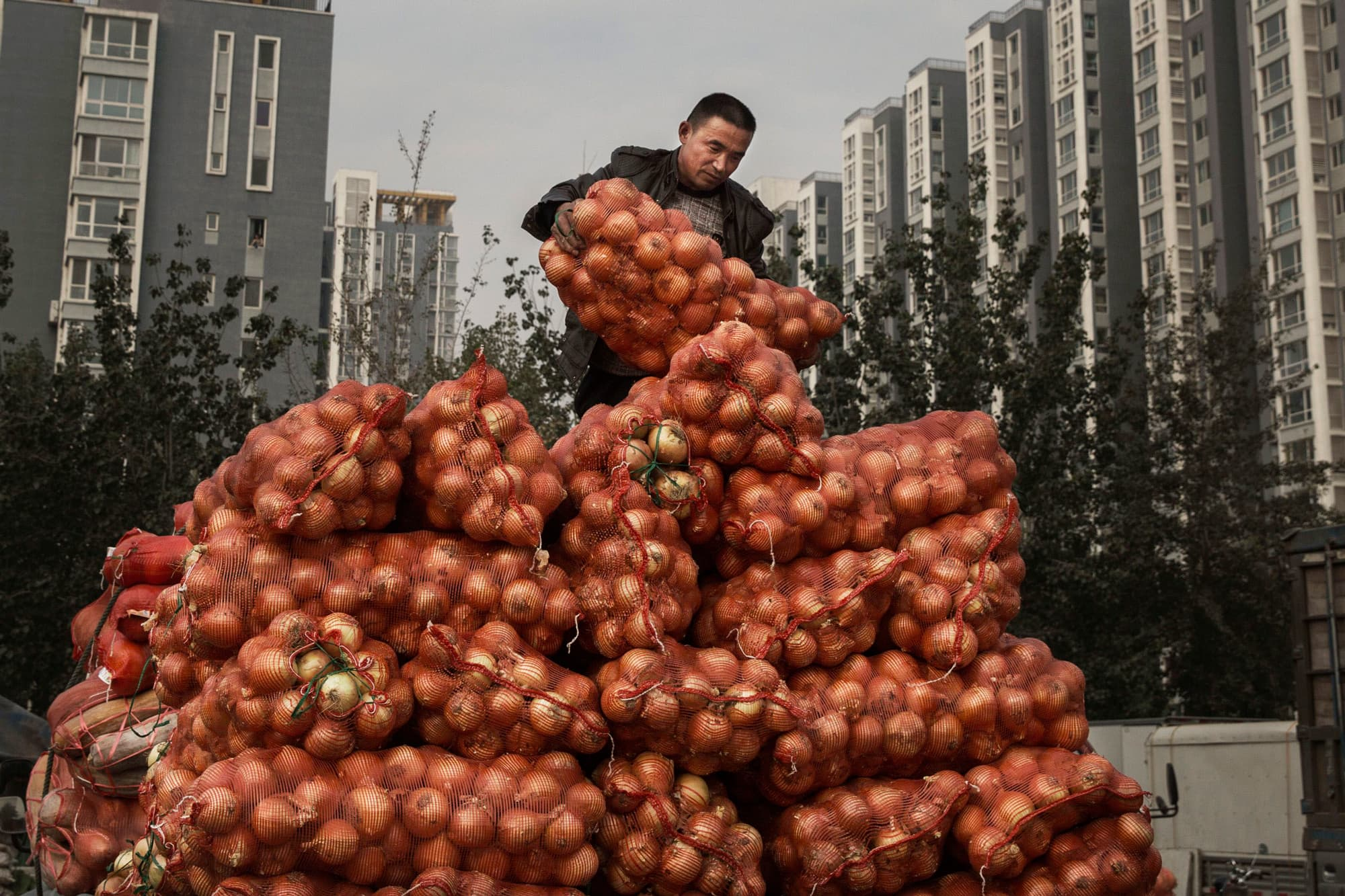 A Chinese vendor unloads onions at a local food market in Beijing.