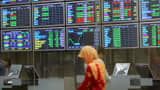 A woman walks past television screens showing stock price index in downtown Kuala Lumpur.
