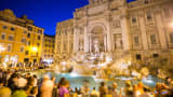 The famous Trevi Fountain in Rome, Italy surrounded by a large crowd of tourists.