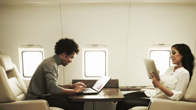 A man and woman read and work on a luxury private jet.