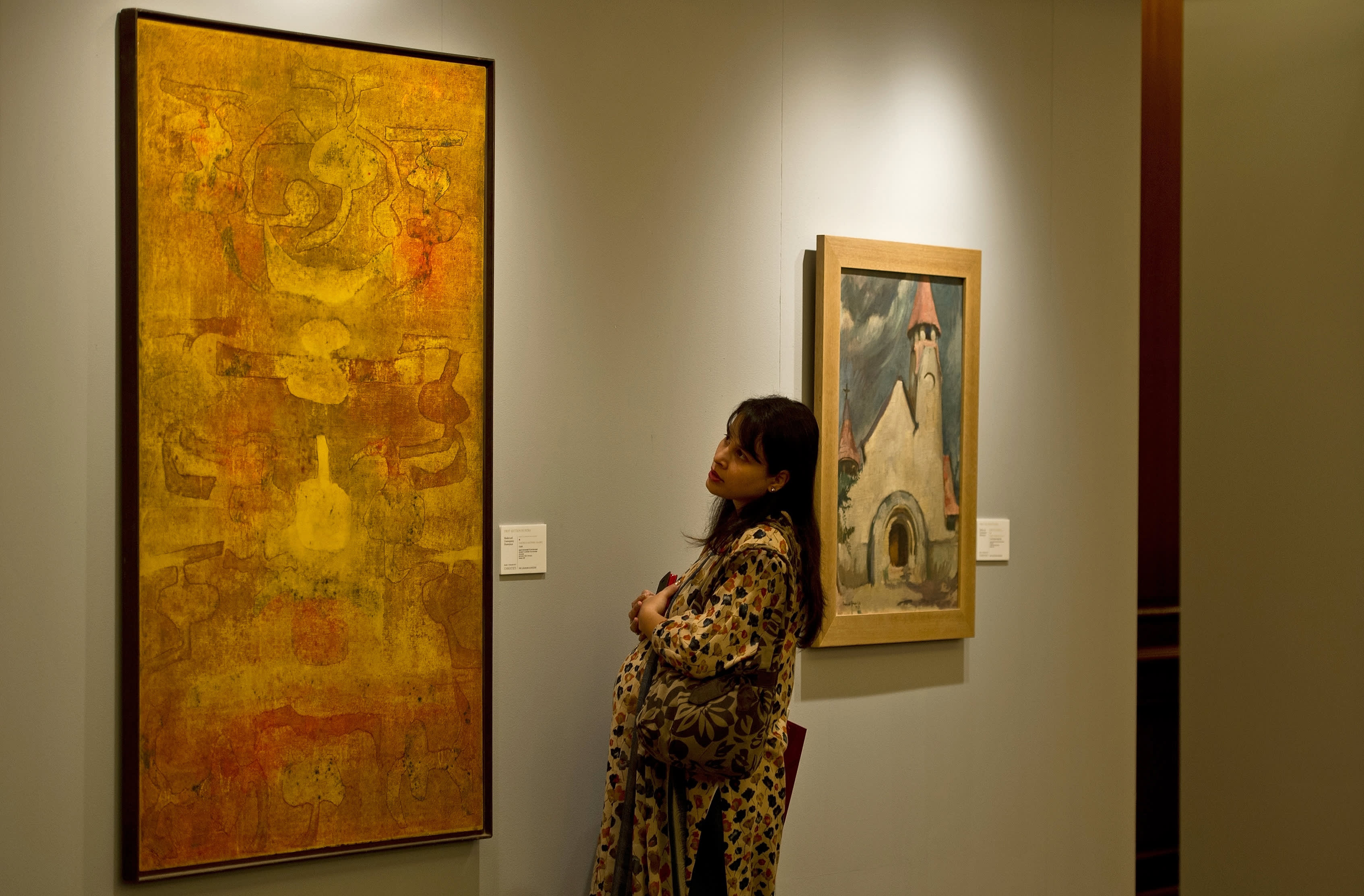 A visitor looks at an untitled painting (L) by Vasudeo S. Gaitonde