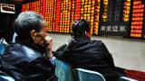 Investors observe stock market at a stock exchange hall