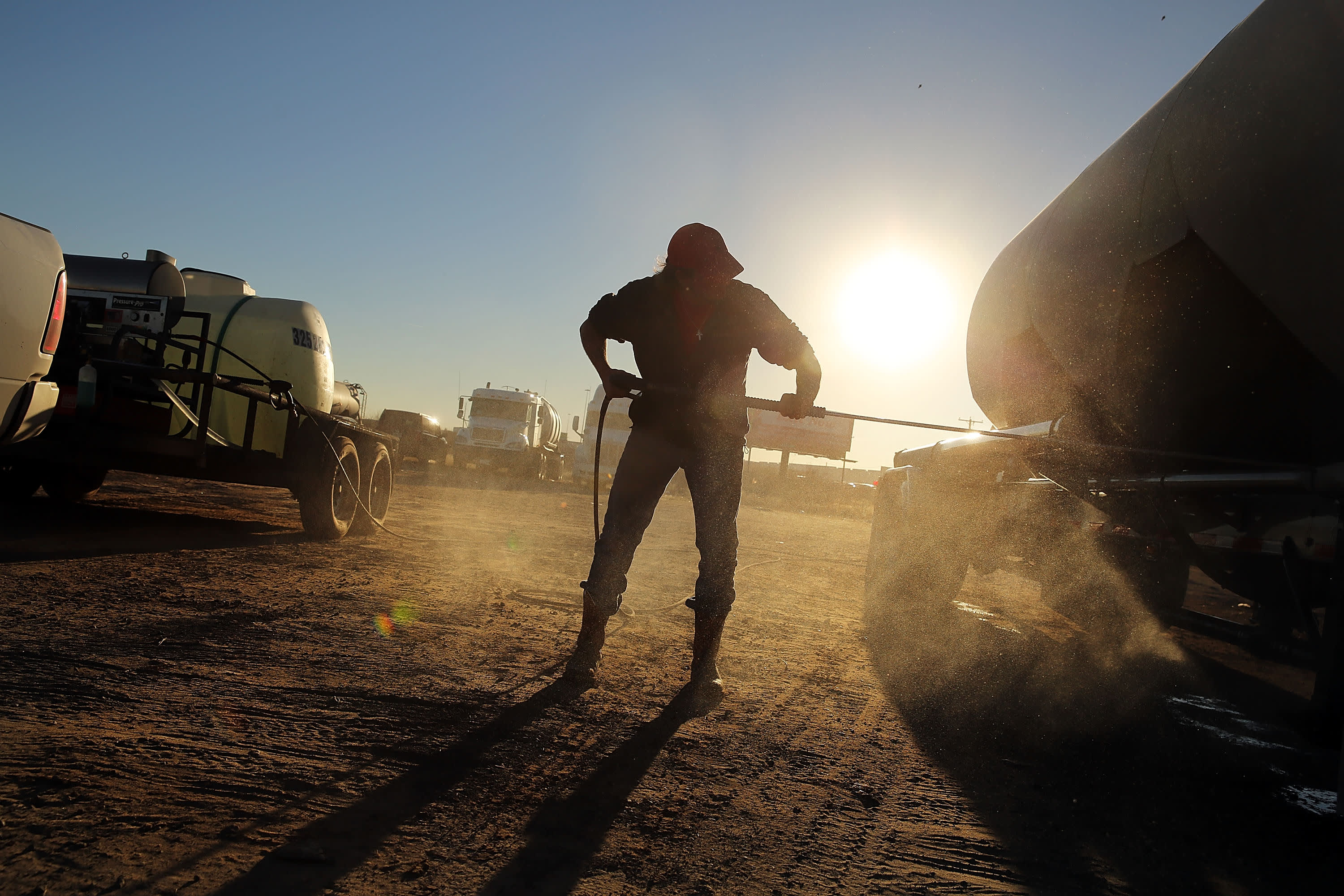 Reusable: Texas oil production fracking worker cleans off truck 150204