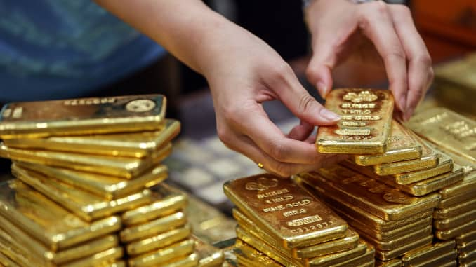 An employee arranges one kilogram gold bars for a photograph at the YLG Bullion International headquarters in Bangkok, Thailand, on Jan. 13, 2016.