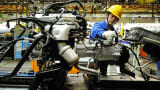 An employee works on an engine at the assembly line of a car factory in Qingdao, China.