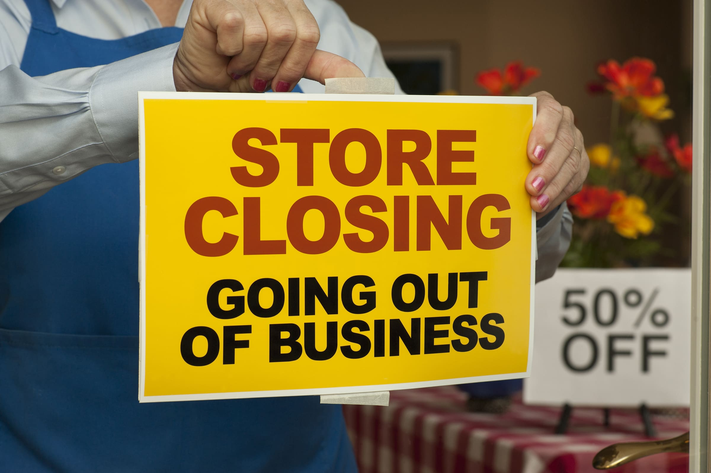 Premium: Store Closing sign being taped on door
