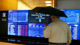 A man looks at the main board of the Australian Securities Exchange ASX.