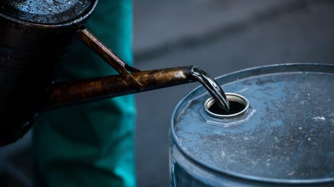 A worker pours liquid oil into a barrel