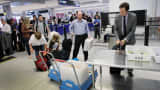 Passengers wait to clear security at Miami International Airport.|