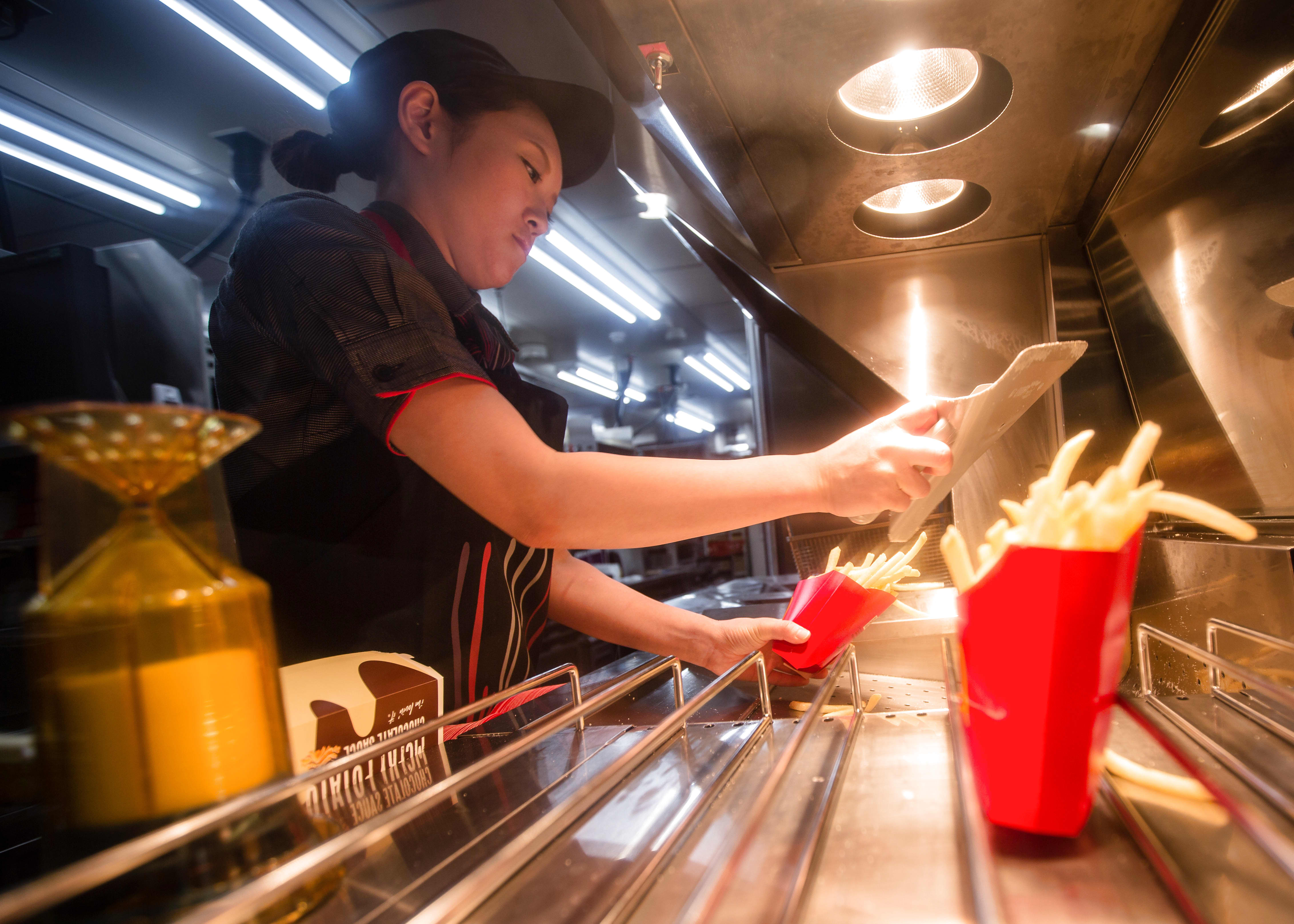 McDonald's worker prepares french fries to go.