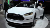 An attendee looks over the Telsa Model X, all electric vehicle, at the Panasonic booth at the 2015 International CES at the Las Vegas Convention Center on January 6, 2015 in Las Vegas, Nevada.