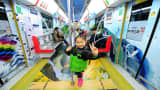 A young girl gives the victory sign on a healthy and happy themed subway train is seen on March 5, 2015 in Hangzhou, Zhejiang province of China.