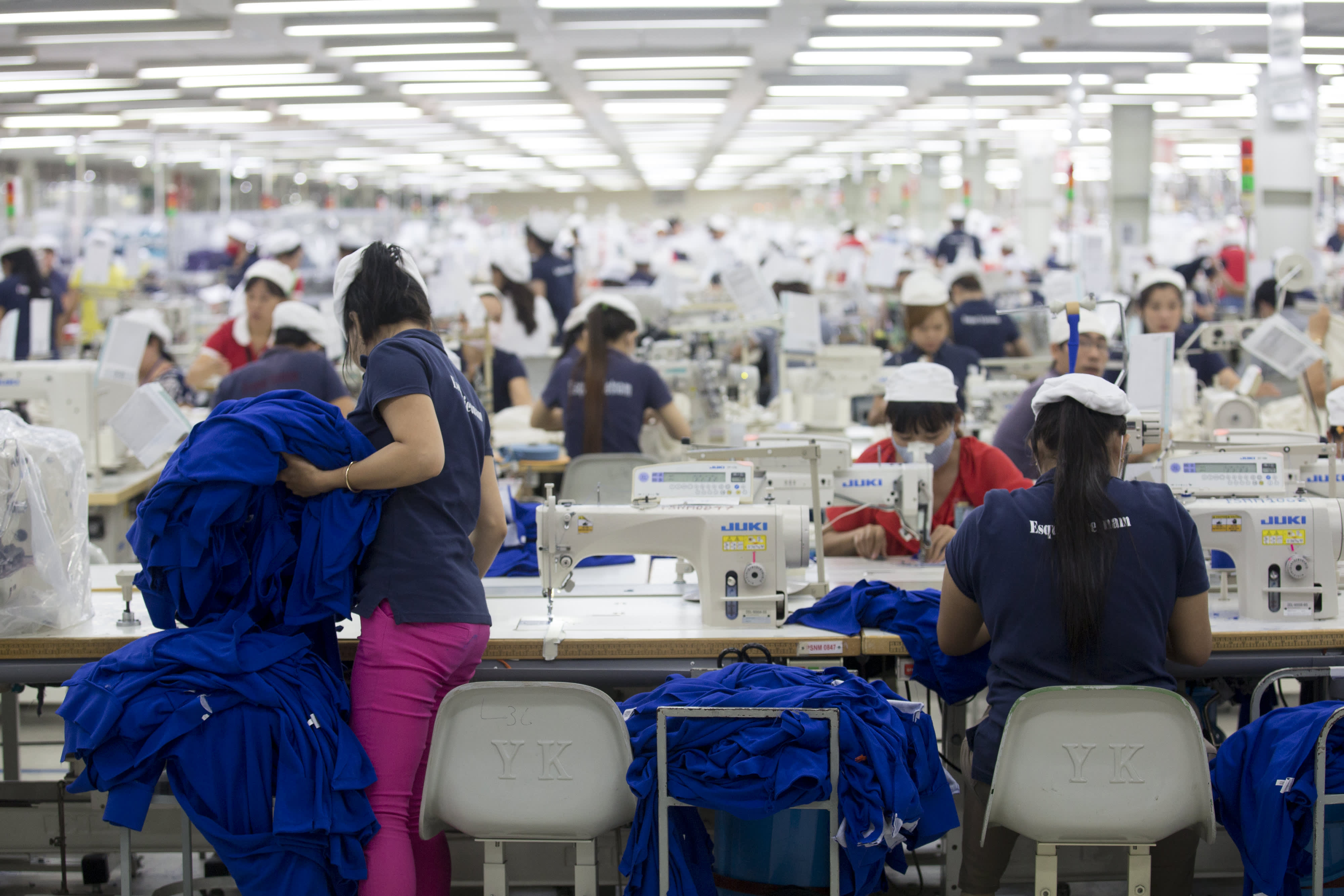 Workers sew clothing at the Esquel Group garment factory at the Vietnam-Singapore Industrial Park in Thuan An, Binh Duong province, Vietnam, in June 2014.