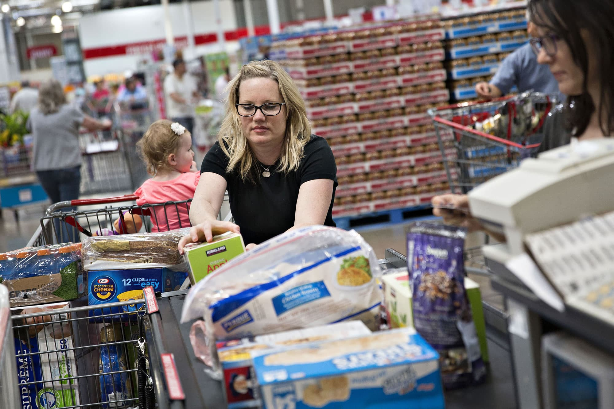 A customer unloads a cart at a cash register at a Costco Wholesale store in Naperville, Illinois.