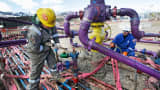 Workers tend to a well head during a hydraulic fracturing operation outside Rifle, Colorado.