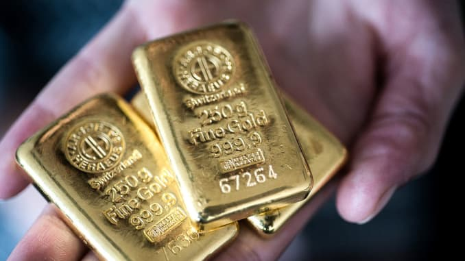 Several gold bars are shown being held in a hand.