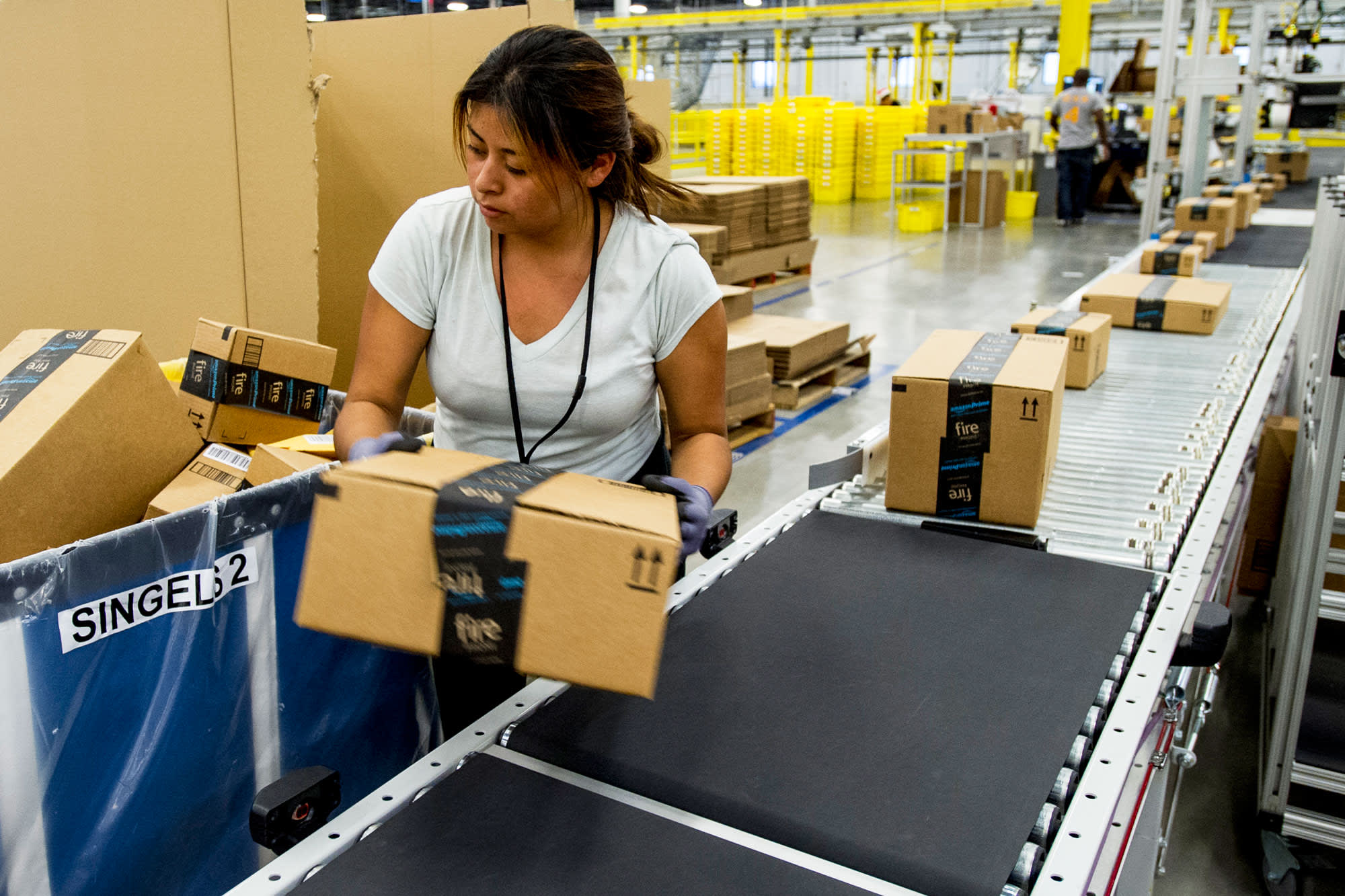 An Amazon.com employee lifts a box from a conveyor at the company's fulfillment center in Tracy, California.