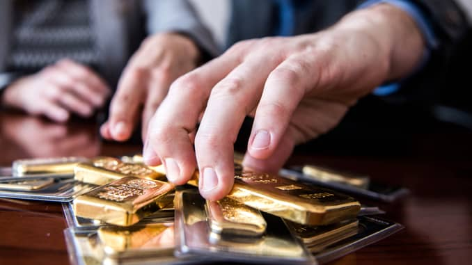 A man counting gold bars.