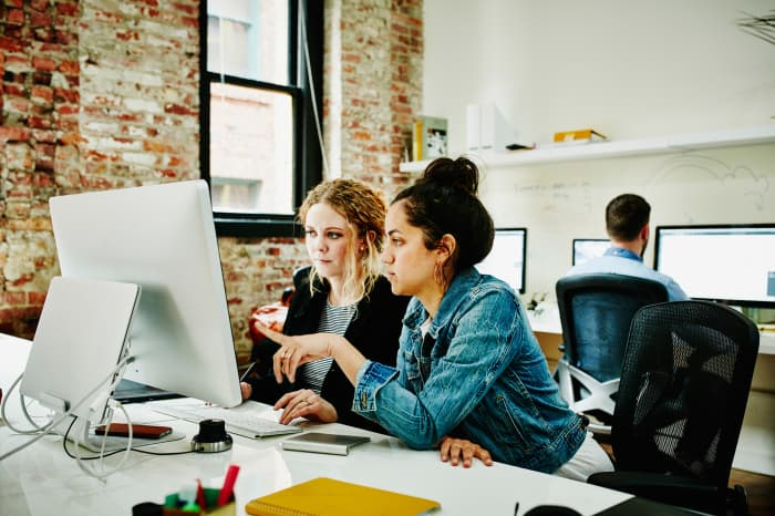 Premium: women in tech working on computers office millennials