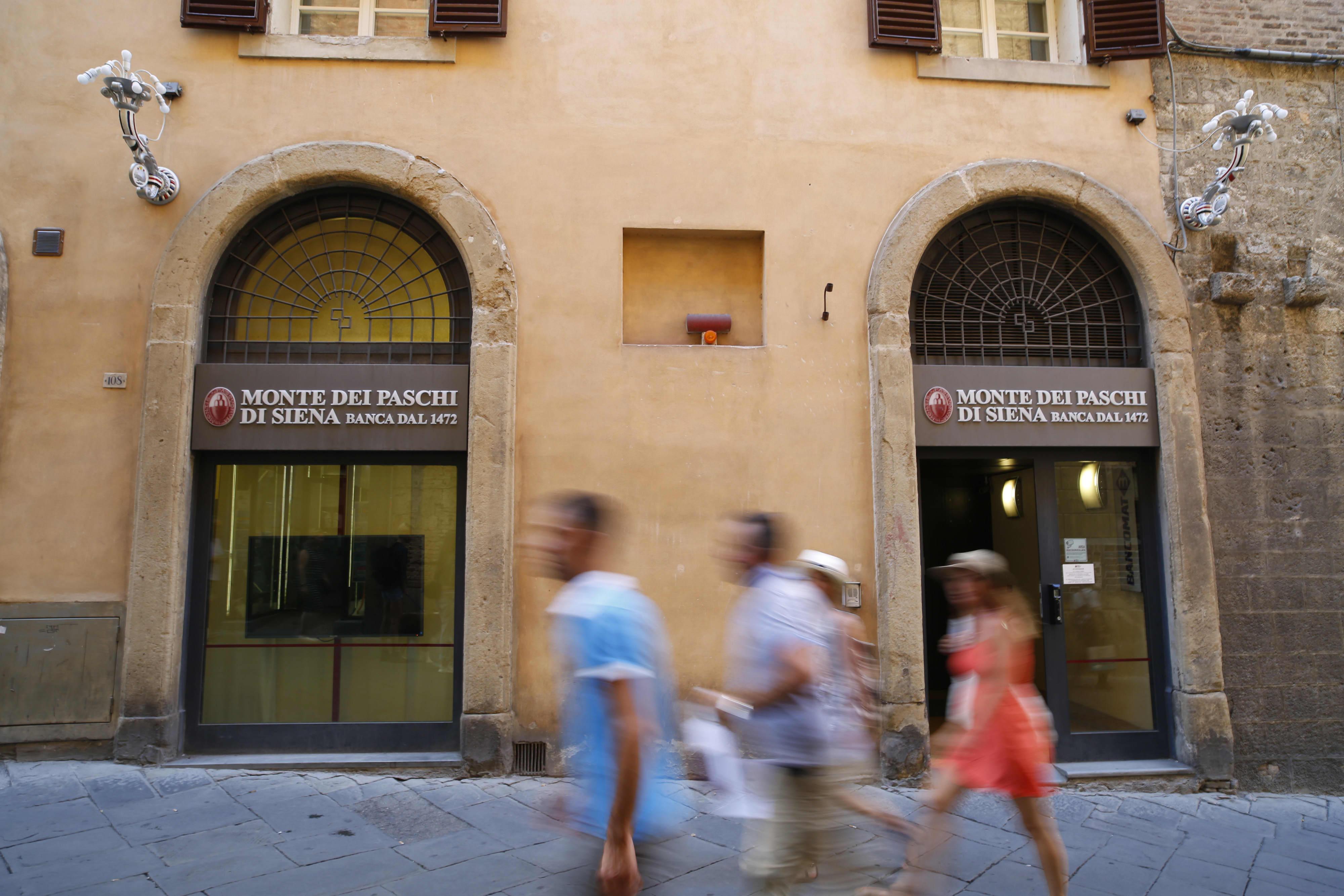 Pedestrians pass by a Banca Monte dei Paschi di Siena bank branch in Siena, Italy.