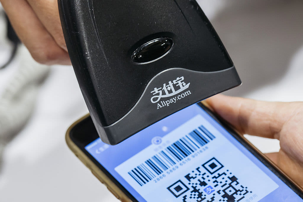 An employee scans a quick response (QR) code displayed on the Ant Financial Services Group's Alipay app, an affiliate of Alibaba Group Holding.