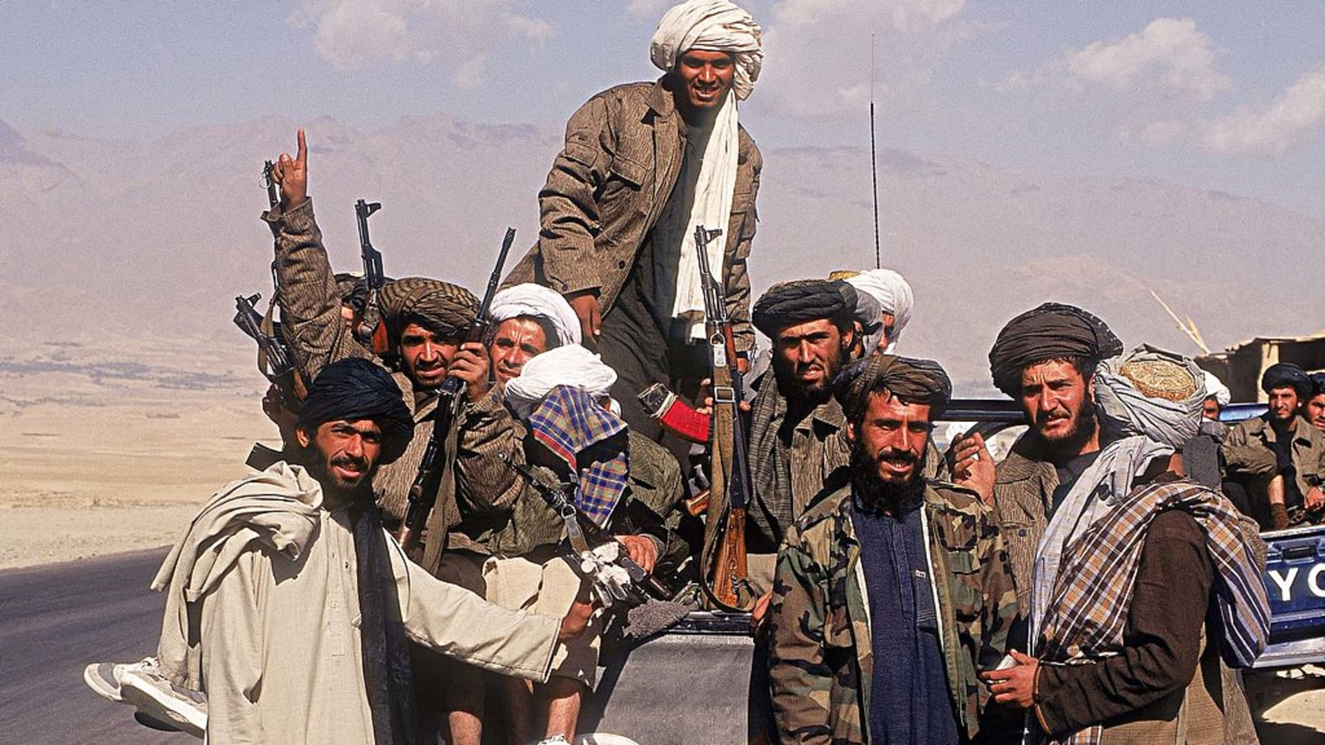 Taliban fighters with a vehicle on a highway in Afghanistan.