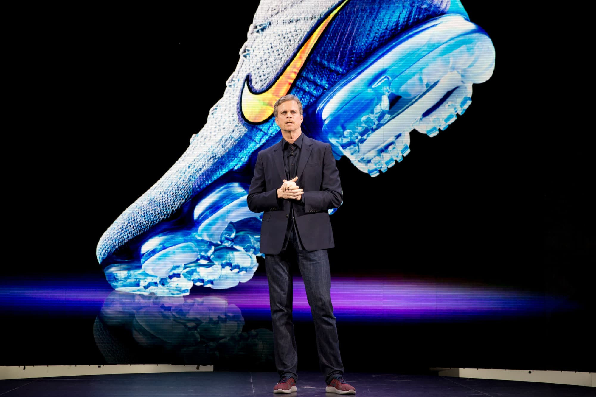An image of the Nike Air VaporMax is projected on a screen as Nike CEO Mark Parker speaks during a news conference, March 16, 2016, in New York.