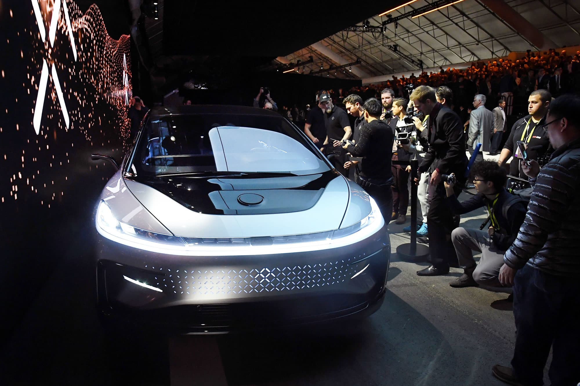 Attendees look at Faraday Future's FF 91 prototype electric crossover vehicle after it was unveiled at CES 2017 on January 3, 2017, in Las Vegas.